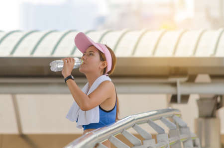 Portrait of woman drinking water on city scape background after exercise. Standard-Bild