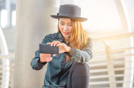 Beautiful lady wear dark green shirt,black hat,using smart phone to selfie with smiling at outdoor.