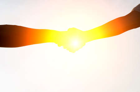 Hand shake with sun set background,silhouette,corporate concept.