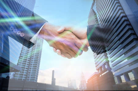 Double exposure of handshake in the cify,business partnership ,success concept,laser.