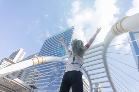 Young lady turn back and raise her hand up to sky in sport wear in the city.