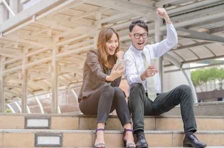 Portrait of an Asian man and woman sitting together and look at their smart phone with smile,buliding background.success concept. Standard-Bild