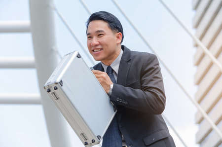 Close up image of asian business man standing,holding breifcase and smile,happy life concept.
