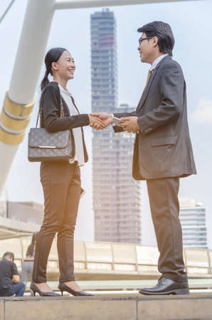 Portrait of business man hold the smart phone on the left hand and  hand shake woman with the city background. Standard-Bild