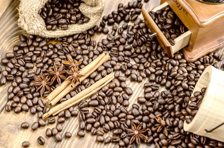 Coffee beans on a wooden table, coffee grinder, cinnamon sticks and anise flowers,wooden spoon.