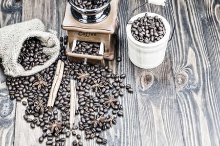 Coffee beans on a wooden table, surrounded by coffee beans, cinnamon sticks and anise flowers,sack,wooden spoon,orange light at front ground. Standard-Bild