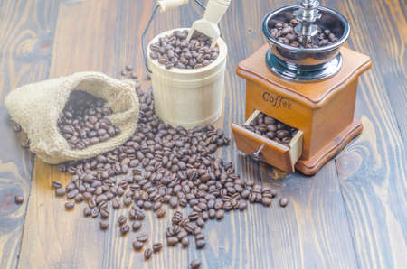 Coffee beans on a wooden table, surrounded by coffee beans, cinnamon sticks and anise flowers,sack,wooden spoon,flowers. Standard-Bild