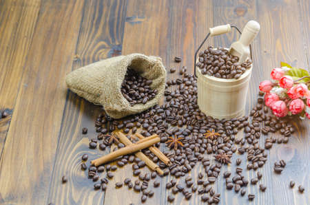 Coffee beans on a wooden table, surrounded by coffee beans, cinnamon sticks and anise flower,coffe in sack,wooden spoon,flower. Standard-Bild