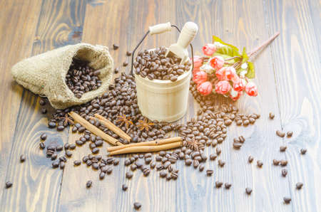 Coffee beans on a wooden table, surrounded by coffee beans,cinnamon sticks and anise flowers,sack,wooden spoon,flower.