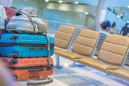 Close up image of many luggages stacking at the airport with passenger seat background,traveling concept,copy space.