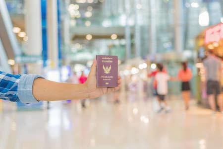 Hand holding Thai passport at the airport with beautiful bokeh background,traveler concept. Standard-Bild