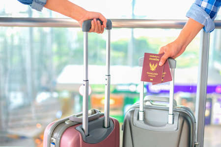 Man's hand hold Passport,Man & Woman hold  luggage, at the airport ,thailand passport The text on that cover means