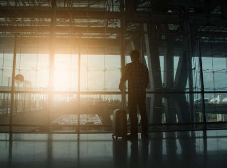 Man standing by the window ,left hand hold the luggage,looking out the door, Silhouette,traveller concept,copy space.