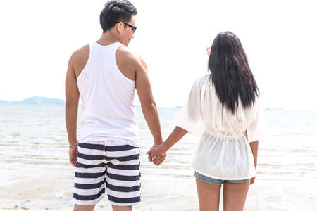 Asian man and woman hold hands together on the beach.