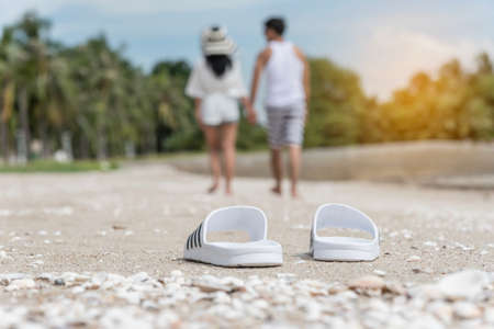 White pair of sandals on the beach with  blurred image of a couple lover walking on the beach on holidays.