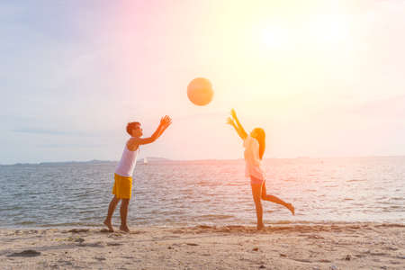 Couple of lovers play ball beach ,beautiful  sunset,holidays concept,copy space.