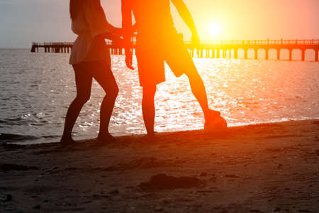Couple of lovers play ball beach ,beautiful  sunset,silhouette,holidays concept,copy space.