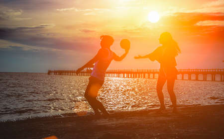 Couple of beautiful lady and hansome man play ball together on beach,sunset,holidays concept,silhouette. Standard-Bild