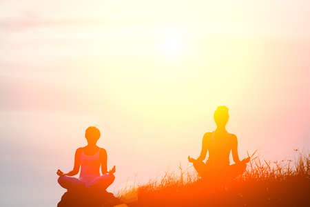 Image of 2 women in meditation poses outdoor,silhouette,sunset,peaceful concept,copy space.