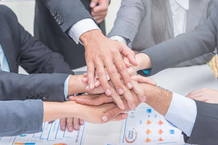 Close up of group of people in suits crossed hands in pile for win closeup, Cooperation initiative achievement, corporate life style, friendship deal, heap, stack concept Standard-Bild
