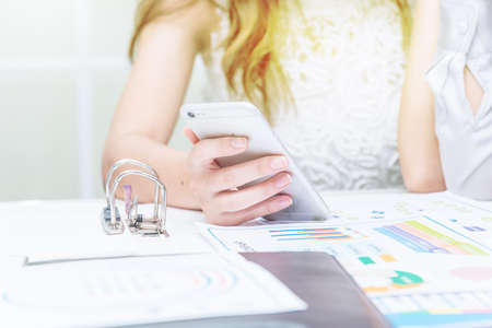 Selective focus of Business woman holding smart phone for online business connection on network technology in office,business and technology concept.