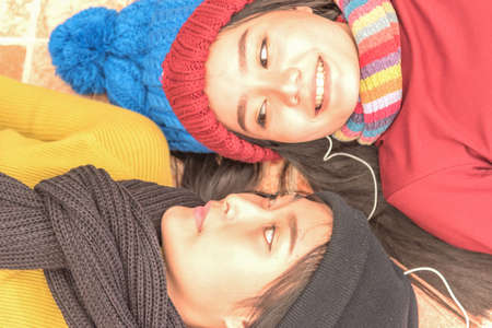Close up of  two teenage girls wear colorful clothes,laying down on floor and smile,winter concept,copy space.