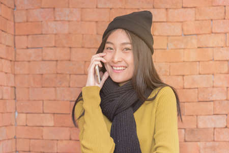 Beautiful Asian woman talking on the smart phone ,technology concept,copyspace. Standard-Bild