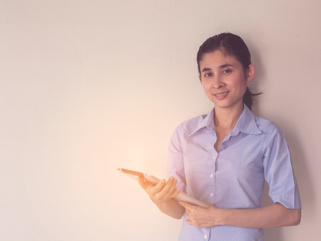 young asian woman standing and holding worksheet and tablet over gray background