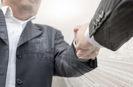 Businessmen shaking hands making an agreement, Double exposure of handshake and city