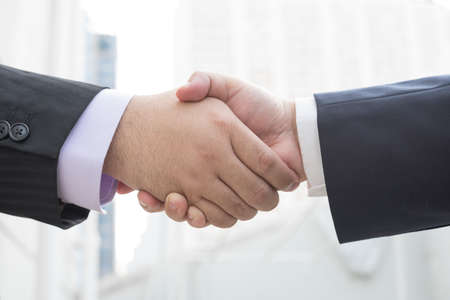 handshake businessmen with blurred building in the background Imagens