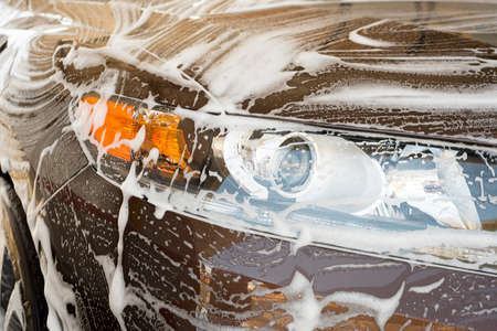 car wash with soap and foam on the front of a brown car Imagens