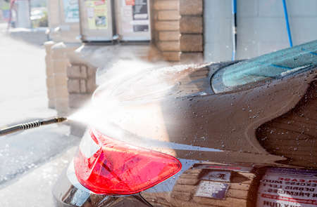 man washing car in sunshine with high pressure washer Imagens
