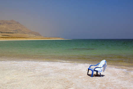 Plastic blue chair on the beach