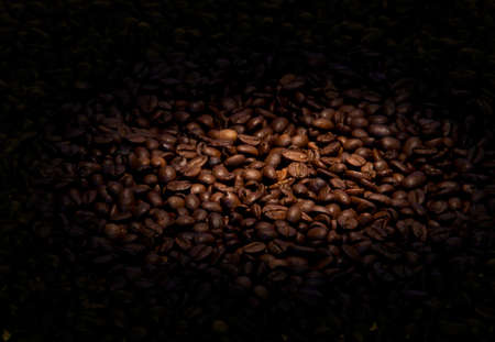 Roasted coffe beans in light spot background