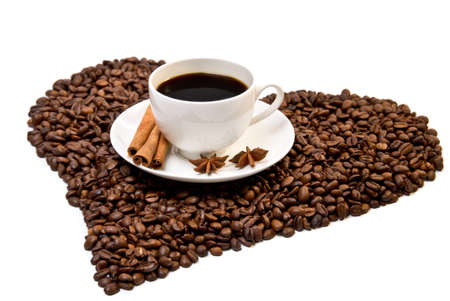 White cup of coffee on heart shaped coffee beans with three sticks of cinnamon and star anise fruits