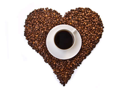 White cup of coffee on heart shaped coffee beans isolated on white background. Top view Stock Photo