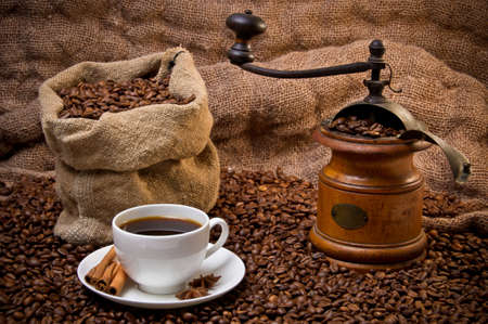 Sack of coffee beans, white cup and coffee-grinder still life. Scattered coffee beans photo