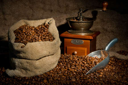 coffee spoon: Sack of coffee beans, coffee-grinder and metal scoop still life. Scattered coffee beans and partial lighting Stock Photo