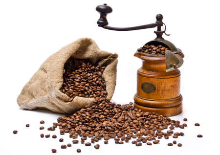Coffee beans sack with scattered beans and old wooden coffee-grinder
