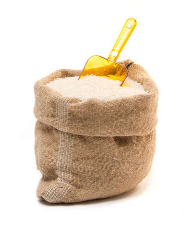 Sack filled with rice and transparent plastic orange scoop isolated on white background photo