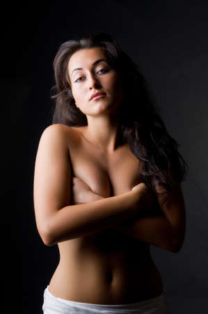 Young dark haired beautiful woman topless with long hair on dark background