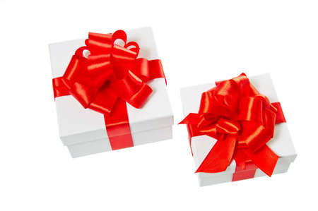 pasteboard: Two white pasteboard square gift boxes with red satin bow and ribbon isolated on white background