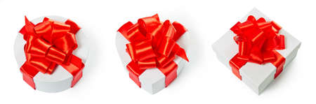 pasteboard: Three white pasteboard square gift boxes with red satin bow and ribbon isolated on white background. Square, round and heart shape. Stock Photo