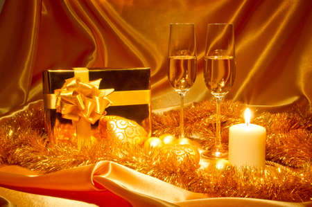 New Year (Christmas) still life in golden tones with gift box, candle, satin, Christmas-tree decorations and two galsses of champagne