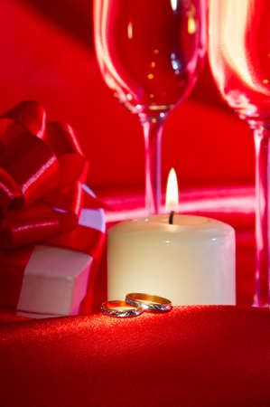 Proposal of marriage still life with two wedding rings, candle, heart shaped gift box and two glasses of champagne. Focus on the wedding rings. photo