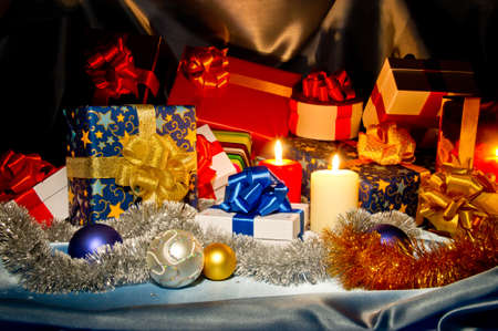 New Year (Christmas) still life with gift boxes, two candles,  sky blue satin and Christmas-tree decorations Stock Photo - 11723889