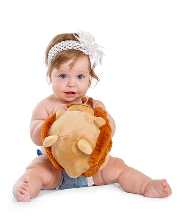 Cute baby girl plays with soft toy on white background
