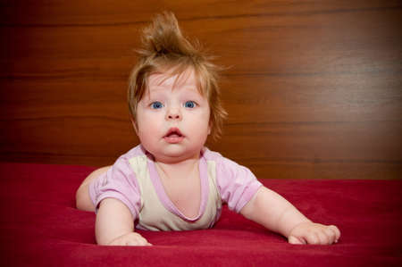 Cute funny touching baby girl with cheerful coiffure
