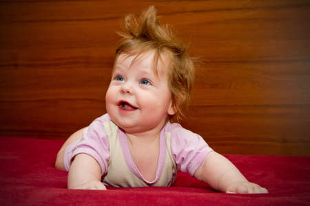 Cute funny touching baby girl with cheerful coiffure smiles Stock Photo - 16305866