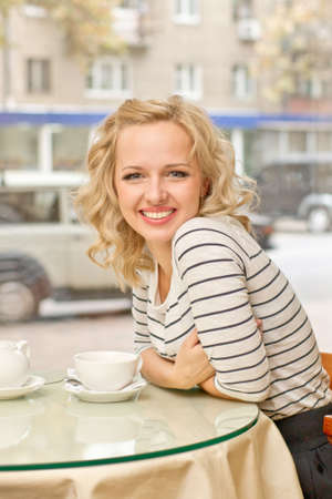 Attractive young blond woman smiles at small cafe Stock Photo - 16932712